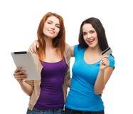 Dos muchachas sonrientes con PC de la tableta y la tarjeta de crédito Fotos de archivo libres de regalías