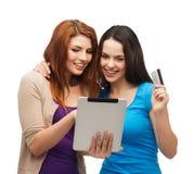 Dos muchachas sonrientes con PC de la tableta y la tarjeta de crédito Imagen de archivo