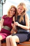 Dos muchachas sonrientes con un teléfono Imagen de archivo
