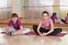 Dos muchachas sonrientes contratadas al entrenamiento físico. Imagen de archivo