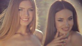 Dos muchachas sonrientes en el bikini que presenta en joyería almacen de video