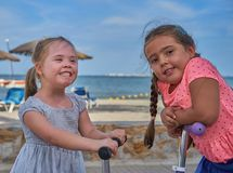 Dos muchachas sonrientes en las vespas por la playa Imagen de archivo