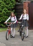 Dos muchachas sonrientes en uniforme escolar que caminan con las bicicletas en str Fotografía de archivo libre de regalías
