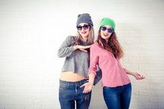 Dos muchachas sonrientes felices del inconformista en la pared blanca Imagen de archivo