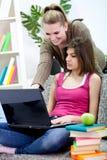 Dos muchachas sonrientes que hacen la preparación usando una computadora portátil. Imagen de archivo