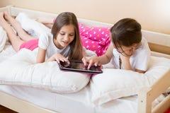 Dos muchachas sonrientes que mienten en cama y que usan la tableta digital Imágenes de archivo libres de regalías