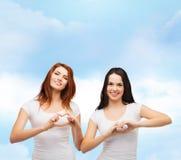 Dos muchachas sonrientes que muestran el corazón con las manos Imágenes de archivo libres de regalías