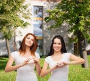 Dos muchachas sonrientes que muestran el corazón con las manos Imagen de archivo libre de regalías