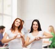 Dos muchachas sonrientes que muestran el corazón con las manos Imagenes de archivo