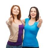 Dos muchachas sonrientes que muestran los pulgares para arriba Imagenes de archivo