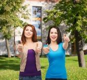 Dos muchachas sonrientes que muestran los pulgares para arriba Foto de archivo