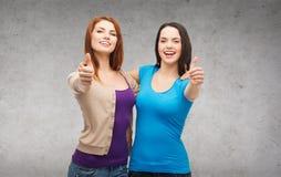 Dos muchachas sonrientes que muestran los pulgares para arriba Imagen de archivo libre de regalías
