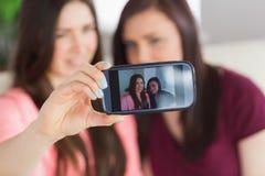 Dos muchachas sonrientes que se sientan en un sofá que toma una foto de ellos mismos con un teléfono móvil Fotos de archivo
