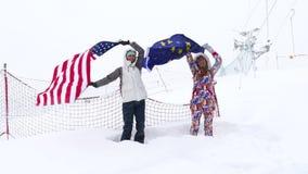Dos muchachas sostienen banderas de la UE y de los E.E.U.U. que agitan en el viento metrajes