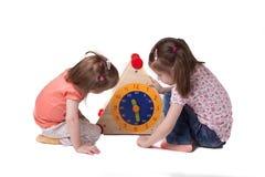 Dos muchachas, tiempo del estudio en sentarse de las horas del juguete imagenes de archivo