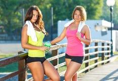 Dos muchachas tienen un resto después de ejercitar al aire libre Imagenes de archivo
