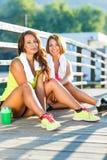 Dos muchachas tienen un resto después de ejercitar al aire libre Imágenes de archivo libres de regalías