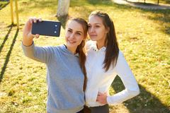 Dos muchachas toman imágenes de Selfie después de entrenar en el aire abierto fresco El hacer se divierte por la mañana y un info Foto de archivo