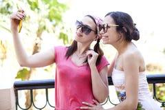Dos muchachas toman imágenes en su teléfono Fotografía de archivo libre de regalías