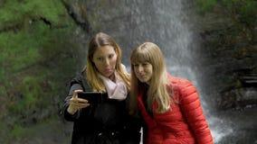 Dos muchachas toman selfies delante de una cascada en Irlanda metrajes