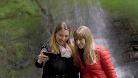 Dos muchachas toman selfies delante de una cascada en Irlanda almacen de video