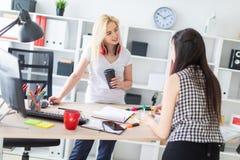 Dos muchachas trabajan en la oficina La muchacha está llevando a cabo un modelo de un hombre imagen de archivo