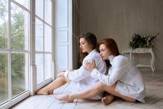 Dos muchachas - una morenita y un pelirrojo están asistiendo en el piso Fotos de archivo libres de regalías