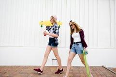 Dos muchachas urbanas con los longboards que llevan las camisas a cuadros que van a lo largo de la calle en la ciudad foto de archivo libre de regalías