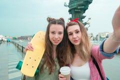 Dos muchachas urbanas del inconformista con el monopatín al aire libre en luz de la puesta del sol Skatebords del primer en manos Imagen de archivo libre de regalías
