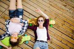 Dos muchachas urbanas jovenes elegantes con longboards mienten en el suelo de madera en la calle Los amigos se divierten y pasan  fotos de archivo libres de regalías
