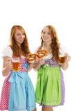 Dos muchachas vestidas bávaras con los pretzeles y la cerveza Imagenes de archivo