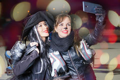 Dos muchachas vestidas suposición feliz hacen el selfie en el teléfono móvil Imagenes de archivo