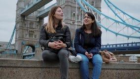 Dos muchachas visitan Londres y gozan del viaje y de visita turística de excursión metrajes