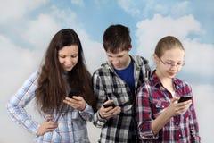 Dos muchachas y compras con los teléfonos celulares Foto de archivo