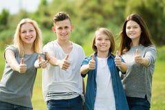 Dos muchachas y dos muchachos que presentan con los pulgares para arriba Imagen de archivo