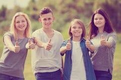 Dos muchachas y dos muchachos que presentan con los pulgares para arriba Imagenes de archivo