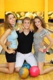 Dos muchachas y el hombre se arrodillan en suelo en club del bowling Fotografía de archivo libre de regalías