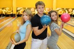 Dos muchachas y el hombre sostienen bolas en club del bowling Imagen de archivo libre de regalías