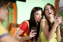 Dos muchachas y el muchacho están bebiendo el vino junto Imágenes de archivo libres de regalías
