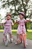 Dos muchachas (3 y 5) en las bicis del empuje Imagenes de archivo