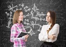 Dos muchachas y fórmulas en la pizarra Fotos de archivo libres de regalías