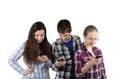 Dos muchachas y muchacho con los teléfonos celulares Foto de archivo