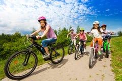 Dos muchachas y muchachos en cascos montan las bicis juntas Imagen de archivo