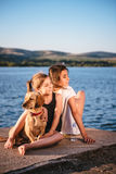Dos muchachas y perros que se sientan por el agua Foto de archivo libre de regalías
