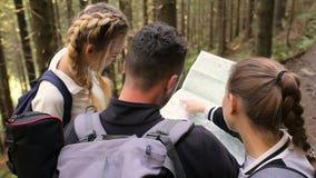 Dos muchachas y un individuo que usa un mapa para encontrar una manera en el bosque almacen de metraje de vídeo