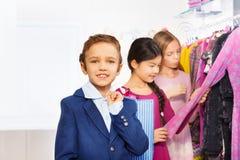 Dos muchachas y un muchacho con el panier en tienda Imagenes de archivo
