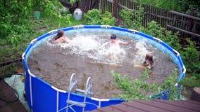 Dos muchachas y un muchacho que salpica en la piscina metrajes