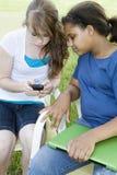 Dos muchachas y un teléfono celular Fotos de archivo