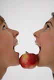 Dos muchachas y una manzana mientras tanto foto de archivo