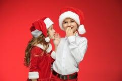 Dos muchacho y muchacha felices en los sombreros de Papá Noel con las cajas de regalo en el estudio Foto de archivo libre de regalías